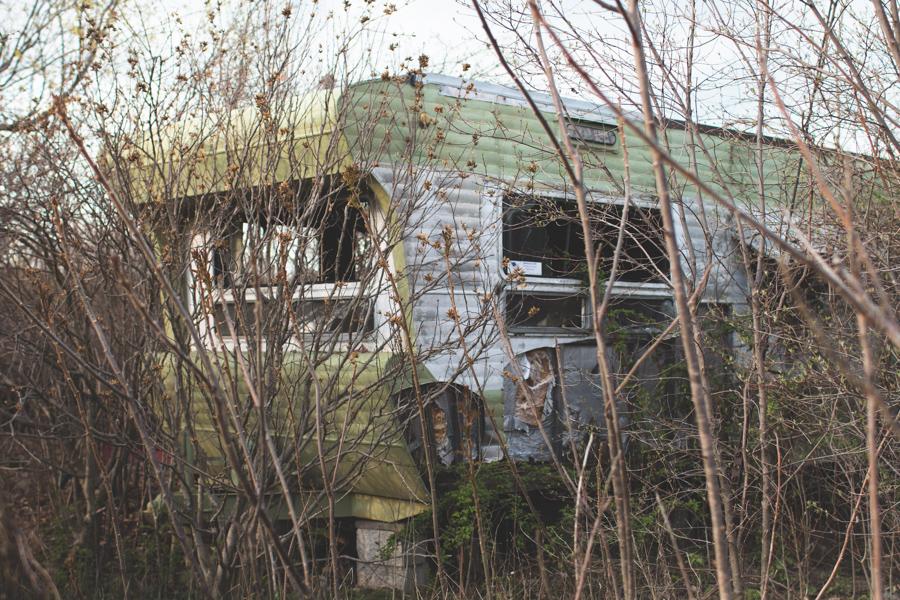green trailer, abandoned, overgrown